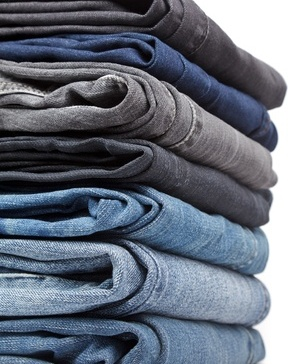 12151698 - stack of blue and black jeans on white background